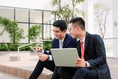 Homme d'affaires dans le costume utilisant l'ordinateur portable et la femme d'affaires utilisant le smartphone devant le b?timen image stock