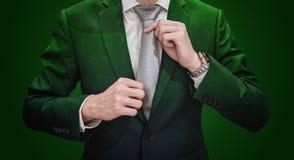 Homme d'affaires dans le costume vert attachant la cravate, sur le fond vert-foncé Affaires environnementales et d'agriculture photographie stock