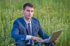 Homme d'affaires dans le domaine, avec un ordinateur portatif Photos stock