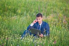 Homme d'affaires dans le domaine, avec un ordinateur portatif Photos libres de droits