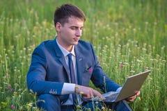 Homme d'affaires dans le domaine, avec un ordinateur portatif Images stock