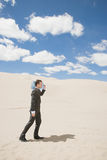 Homme d'affaires dans le désert avec la bouteille Photographie stock