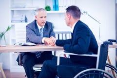 Homme d'affaires dans le fauteuil roulant parlant avec le collègue Image stock