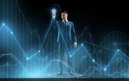 Homme d'affaires dans le graphique virtuel émouvant de costume Photographie stock libre de droits