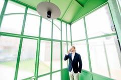 Homme d'affaires dans le hall vert images stock