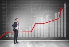 Homme d'affaires dans le lien et les graphiques rouges Images stock
