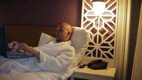 Homme d'affaires dans le peignoir se trouvant sur le lit dans l'hôtel et à l'aide de l'ordinateur portable banque de vidéos