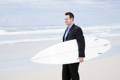 Homme d'affaires dans le procès avec la planche de surfing sur la plage Images stock