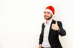 Homme d'affaires dans le procès avec le chapeau de Santa sur la tête D'isolement au-dessus du fond blanc Photographie stock libre de droits
