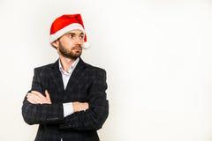 Homme d'affaires dans le procès avec le chapeau de Santa sur la tête D'isolement au-dessus du fond blanc Photo libre de droits