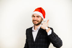 Homme d'affaires dans le procès avec le chapeau de Santa sur la tête D'isolement au-dessus du fond blanc Photos libres de droits
