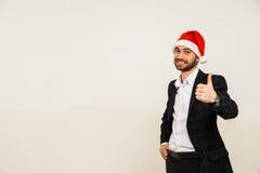 Homme d'affaires dans le procès avec le chapeau de Santa sur la tête D'isolement au-dessus du fond blanc Image libre de droits