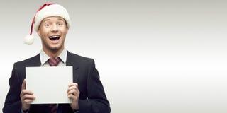 Homme d'affaires dans le signe de fixation de chapeau de Santa Images stock