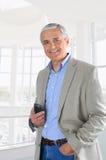 Homme d'affaires dans le téléphone portable hodling de configuration de bureau Photographie stock