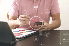 homme d'affaires dans le T-shirt rose fonctionnant avec le téléphone et le digitl futés Photo libre de droits