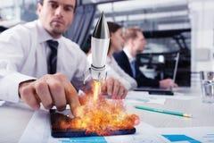 Homme d'affaires dans le travail de bureau pour un démarrage d'une société avec une fusée Image stock