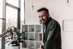 Homme d'affaires dans les vêtements décontractés souriant à l'appareil-photo dans le bureau moderne Photos stock