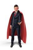 Homme d'affaires dans un cap rouge et un masque d'oeil rouge regardant sa main et tenant quelque chose sur le fond blanc Images stock