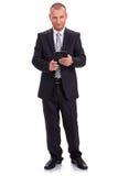 Homme d'affaires dans un costume foncé, tenant un comprimé, consultant la La Photos libres de droits