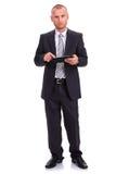 Homme d'affaires dans un costume foncé, tenant un comprimé, consultant la La Photos stock