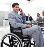 Homme d'affaires dans un fauteuil roulant au cours d'un contact photographie stock