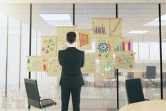 Homme d'affaires dans un lieu de réunion ensoleillé regardant les diagrammes financiers images libres de droits