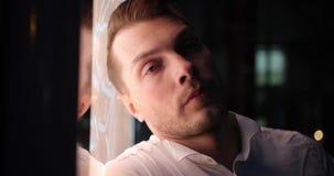 Homme d'affaires dans un voyage Le jeune homme d'affaires bel fatigué se penche à un écran tandis qu'il attend un taxi dehors banque de vidéos