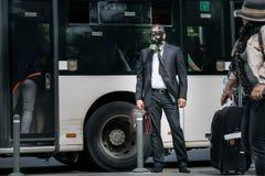 Homme d'affaires dans une gare routière utilisant un masque de gaz Images libres de droits