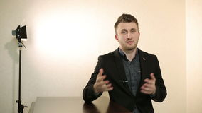 Homme d'affaires dans une veste noire et une chemise foncée parlant quelque chose à l'appareil-photo clips vidéos