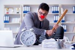 Homme d'affaires de clown dans le bureau avec la batte de baseball et une alarme c Photos libres de droits