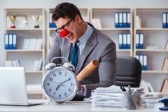 Homme d'affaires de clown dans le bureau avec la batte de baseball et une alarme c Images stock