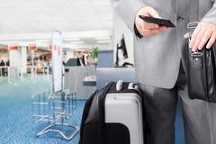Homme d'affaires de déplacement appelant par le téléphone à l'aéroport Image libre de droits