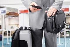 Homme d'affaires de déplacement appelant par le téléphone à l'aéroport Images stock