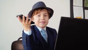 Homme d'affaires de garçon avec le téléphone à disposition se reposant dans le bureau souriant et travaillant près de l'ordinateu clips vidéos