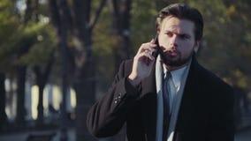 Homme d'affaires de Hansome parlant au téléphone en parc banque de vidéos