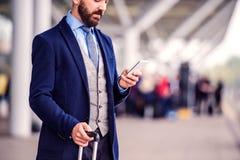 Homme d'affaires de hippie avec le téléphone intelligent attendant à l'aéroport Image libre de droits