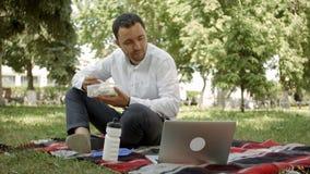 Homme d'affaires de hippie buvant une tasse de café dans le café de ville pendant le temps de déjeuner Il travaille sur l'ordinat Photo libre de droits