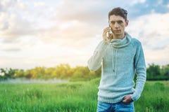 Homme d'affaires de jeune homme parlant au téléphone portable dehors sur un champ d'herbe Photographie stock