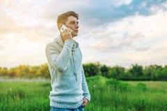 Homme d'affaires de jeune homme parlant au téléphone portable dehors sur un champ d'herbe Photographie stock libre de droits