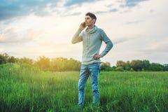 Homme d'affaires de jeune homme parlant au téléphone portable dehors sur un champ d'herbe Images stock