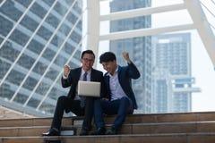 Homme d'affaires de l'Asiatique deux heureux tout en situant voir l'ordinateur portable dans le busi images stock
