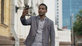 Homme d'affaires de métis ayant la causerie visuelle en ligne dans la conférence d'affaires utilisant le smartphone banque de vidéos