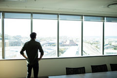 Homme d'affaires de PF de vue arrière regardant par la fenêtre le lieu de travail photos stock