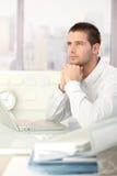 Homme d'affaires de rêverie s'asseyant au bureau Photographie stock libre de droits
