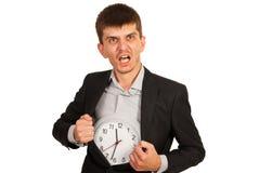 Homme d'affaires de rage avec l'horloge dans le manteau Images stock