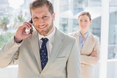 Homme d'affaires de sourire au téléphone regardant l'appareil-photo Image libre de droits