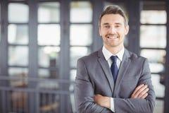 Homme d'affaires de sourire avec des bras croisés dans le bureau Photo libre de droits