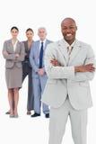 Homme d'affaires de sourire avec des bras pliés et équipe derrière lui Image libre de droits