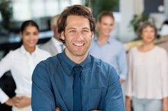 Homme d'affaires de sourire avec des collègues Photo stock