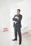 Homme d'affaires de sourire avec des documents à une maison à vendre Images libres de droits